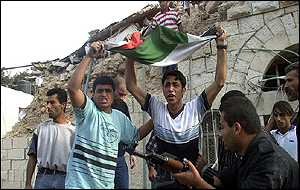 Palestinian youths demonstrate in the rubble of Ramallah police station