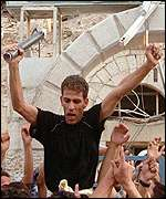 Palestinian holds up part of an Israeli missile