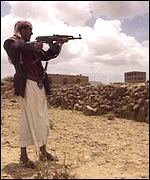 A Yemeni tribesman aims his gun