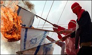 Palestinian protesters burn the Israeli flag at a refugee camp in the Gaza strip