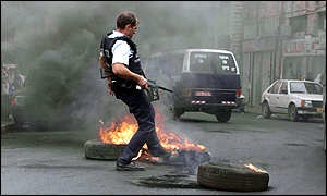 A policeman kicks out burning tyres in Jerusalem