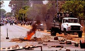 Police truck drives round a burning barricade