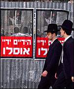 Orthodox Jews pass posters of the killings