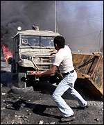 Palestinian protester throws stones at Israeli army jeep