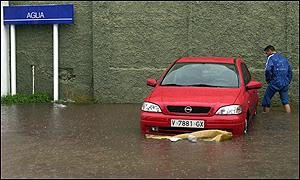 A submerged car in a petrol station in Valencia. The sign reads water