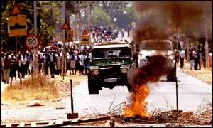 Zimbabwe riot police vehicles approach a burning barricade in Mabvuku