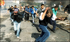 Palestinian youths flee teargas