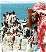Yemenis watching the ship leaving from the port
