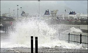 Waves crash against Dover promenade with the harbour in the background