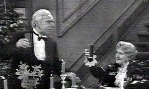 image: [ Butler James (Freddie Frinton) toasts Sophie (May Warden) in Dinner for One ]