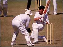 David Boon sweeps the ball away